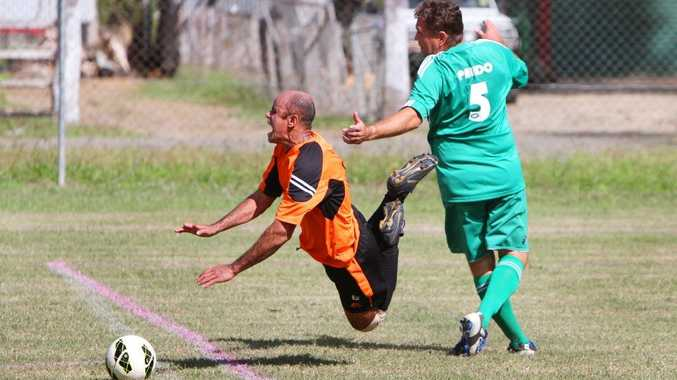 Beavers P Turnber trips Cap Coast Jose Wilson in the Capricorn Coast v Beavers from Brazil at the over 35 soccer tournament at Elizabeth Park on Saturday. Photo: Chris Ison / The Morning Bulletin