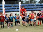Shane Crawford takes some of the Auskick kids for a run.