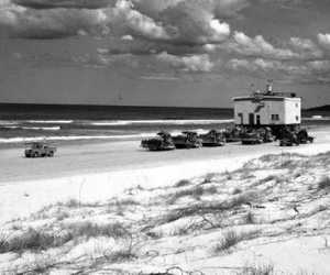 Bulldozers move a sand-mining plant along Tallow Beach.