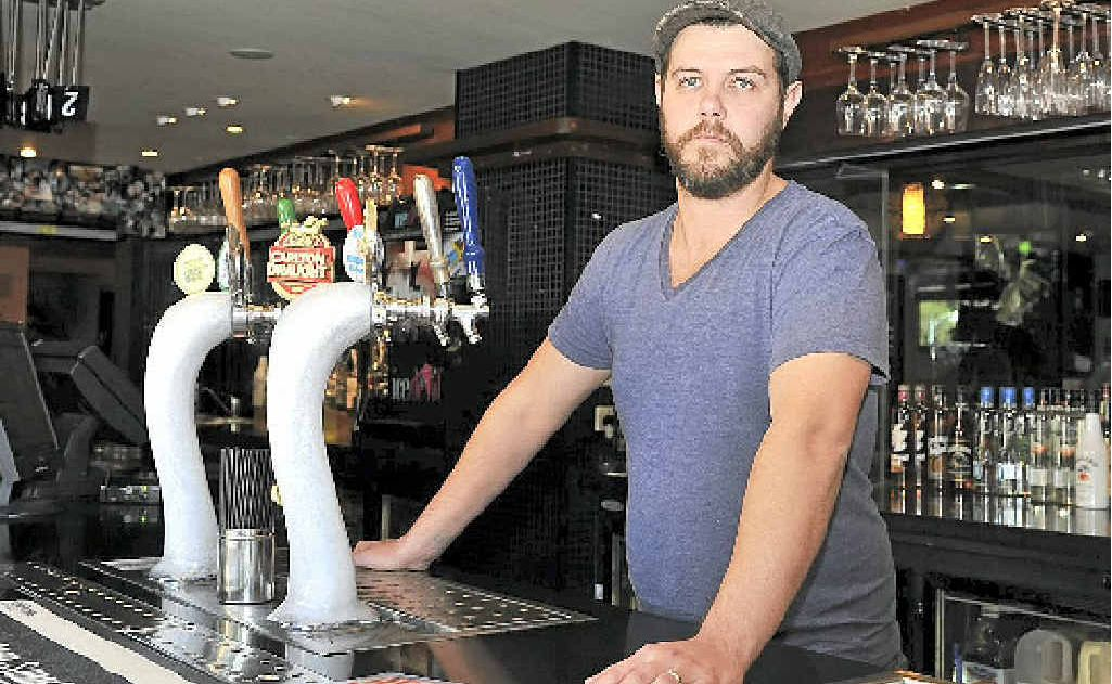 MISUNDERSTANDING: Food and beverage manager Chris Schneider behind the bar at Aquarius Backpackers in Byron Bay.