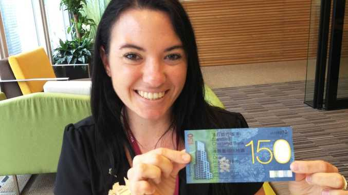 St George Bank Tweed City employee Simone Millar checks out a limited edition $150 HKD note in Hong Kong, China