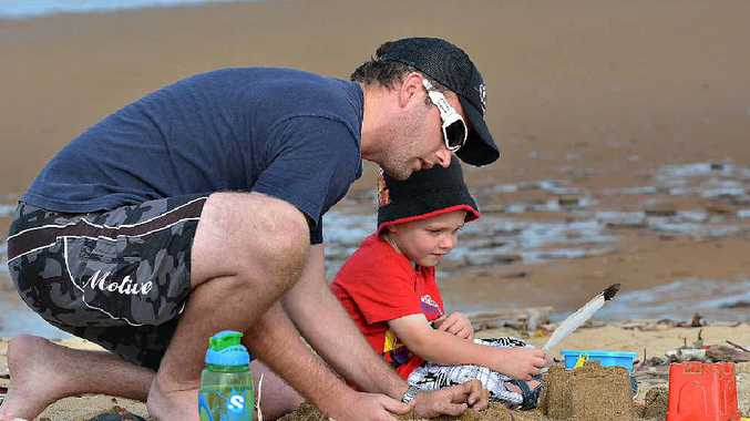 BUILDING FRIENDSHIP: Joel Winters and his son Connor build castles in the sand at Mackay.