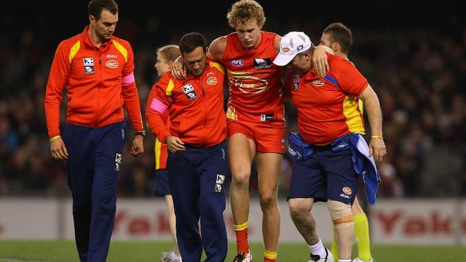 Tom Lynch of the Suns is helped from the ground after colliding with Jake Melksham of the Bombers during the round 12 AFL match between the Essendon Bombers and the Gold Coast Suns at Etihad Stadium on June 15, 2013 in Melbourne, Australia.