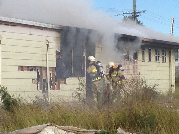 Firefighters inspect a shed on fire in Pialba.
