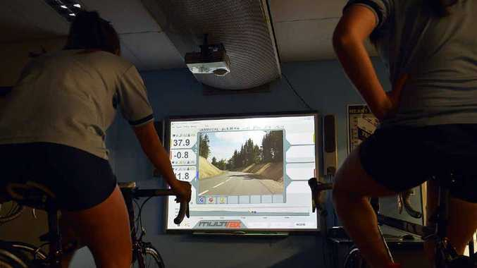 GO FOR SPIN: A student is silhouetted as she cycles on a stationary bicycle while watching a video of a French cycle route.