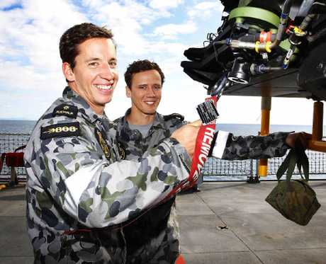 TECH WORK: Two naval aviation technicians who are both able seamen and lifelong mates, Daniel Weier and Grant Hatchman, work on an MRH90 helicopter aboard HMAS Choules.