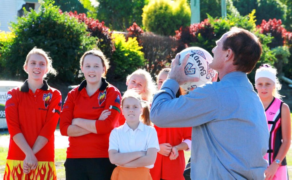CHANGING TACT: Sport Minister Steve Dickson playing a quick match with the local Bundy Flames at Daph Geddes Park, Netball Queensland has cut the 'Everyone Gets A Ribbon Culture' from its events. Photo: Zach Hogg / NewsMail