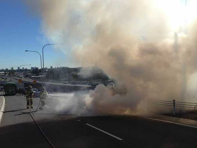 Tweed Heads Fire Brigade senior firefighters Bruce Ransome and Greg Mackay battle the BMW blaze on Sexton Hill.