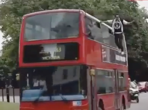 Magician sails through London mid-air on the side of a bus