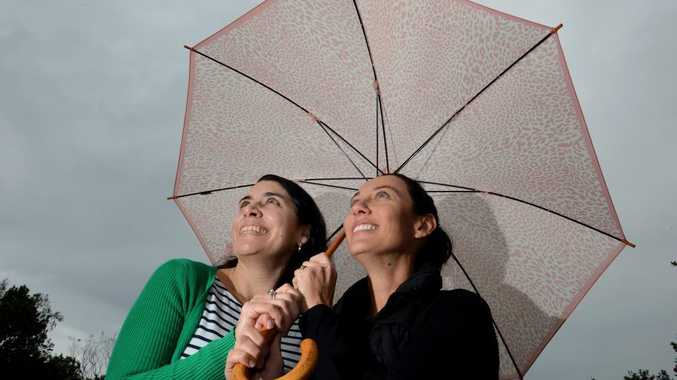 Peta Fahy and Janene Barwick keep out of the rain in Kingscliff.