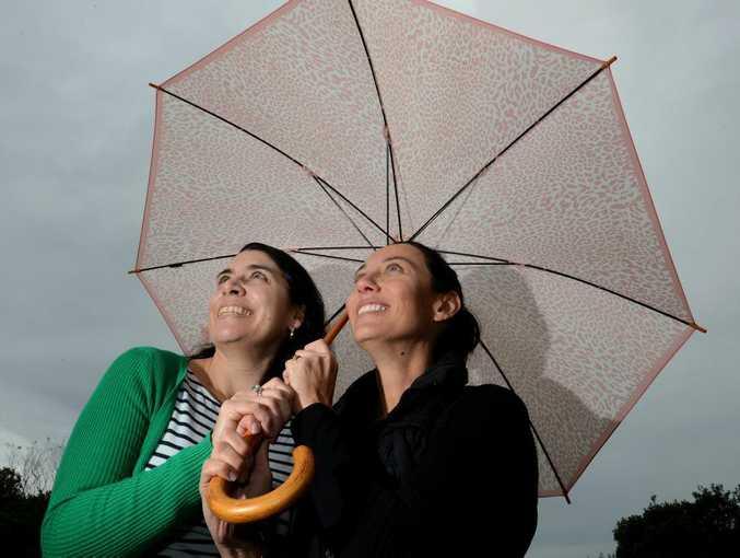 Peta Fahy and Janene Barwick keep out of the rain in Kingscliff.