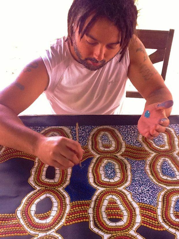 Bundjalung Kunjiel manager and performer Stephen Larcombe works on his artwork.