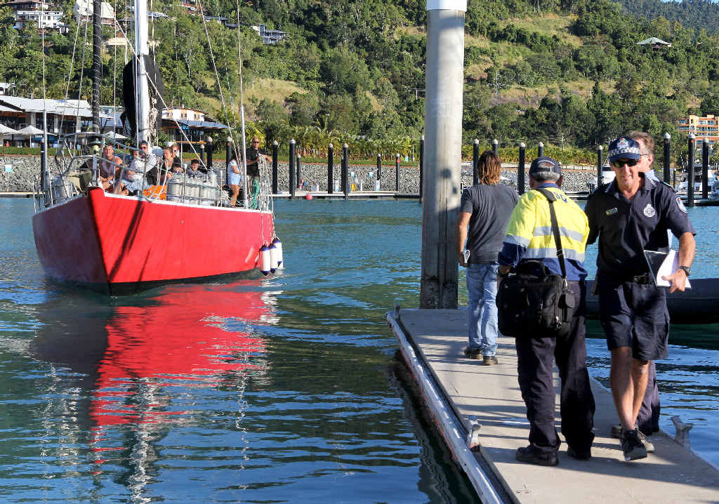 The Samurai comes into Abell Point Marina as Whitsunday Water Police officers and MSQ staff wait to board the boat. The vessel's owner Rick Sampara is walking towards the boat.