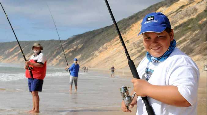 Eleven-year-old Joshua Fischer, who travelled all the way from South Africa to Rainbow Beach for the Rainbow Beach Family Fishing Classic. His granddad Leo Fischer is in the background.