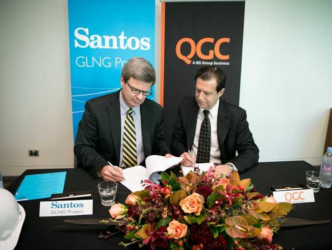 Santos Vice President GLNG Downstream Rod Duke (left) and QGC's Derek Fisher sign an agreement to link pipelines on Curtis Island.