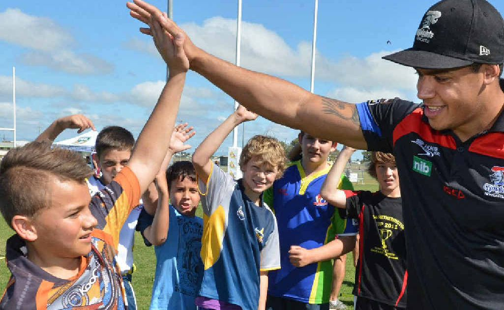 Mackay's Lincoln Baker gives Knights centre Dane Gagai a high five after completing a skills session.