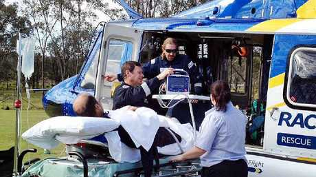 SWIFT RESPONSE: The RACQ CareFlight rescue crew prepares to transport a man with a severed foot yesterday.