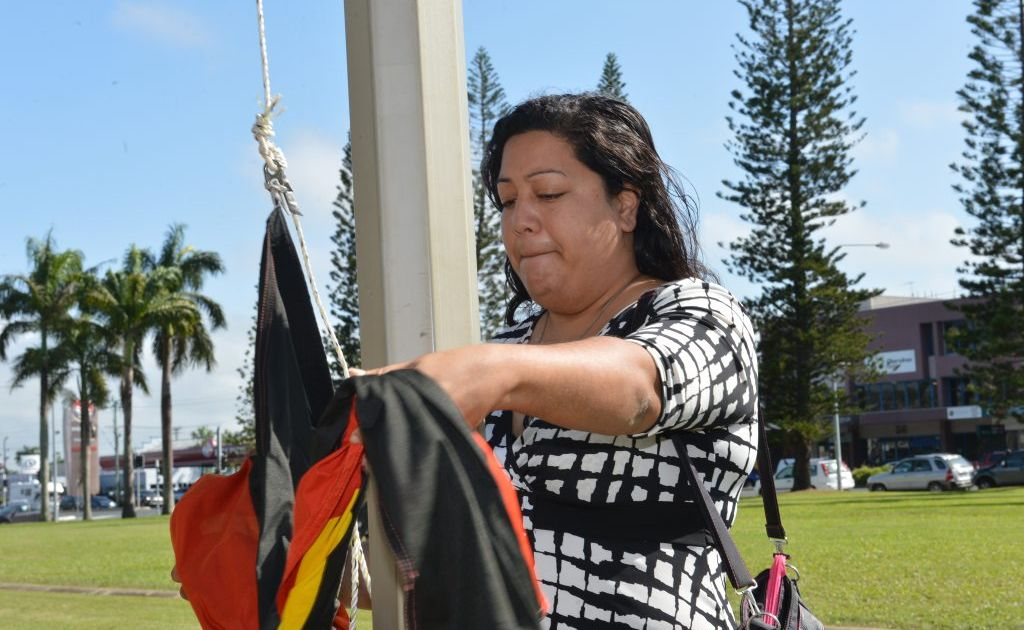Melanie Kemp raises the Aboriginal flag for NAIDOC week in Mackay.