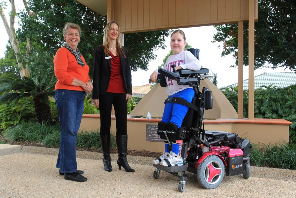 Members of Maroochydore's Allora Gardens Retirement Village have raised almost $9,000 to help 11-year-old Chancellor State College student Breanna Medcalfe purchase a new wheelchair that allows her to stand at the touch of a button. Breanna is pictured with her mum, Marie, and Val Bartlett, chairperson of the residents committee. Photo: Brett Wortman / Sunshine Coast Daily