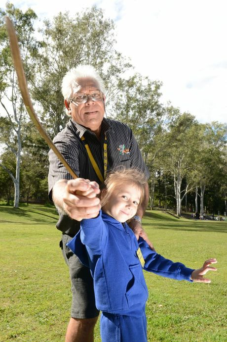 Uncle Bill Bonner demonstrating how to throw a boomerang to Angelique Bradley from Ipswich West State School as part of NAIDOC Week celebrations at Ipswich Central State School on Tuesday.