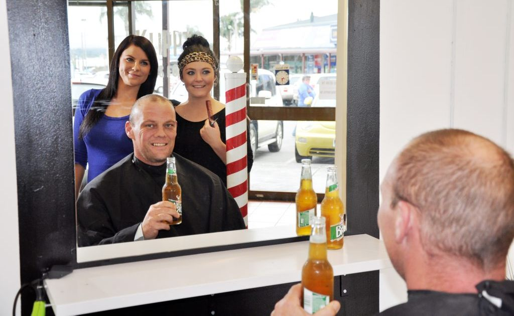 Matt Bingham drops into Hooper Centre barbershop Klippt for a shaved head and a frosty-cold beer, under the expert hands of Ashleigh Gordon (left) and Amanda Beth.