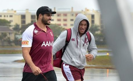 Queensland State of Origin team arrive at the Sunshine Coast Airport. Greg Inglis and Josh Papalii brave the rain. Photo: Warren Lynam / Sunshine Coast Daily
