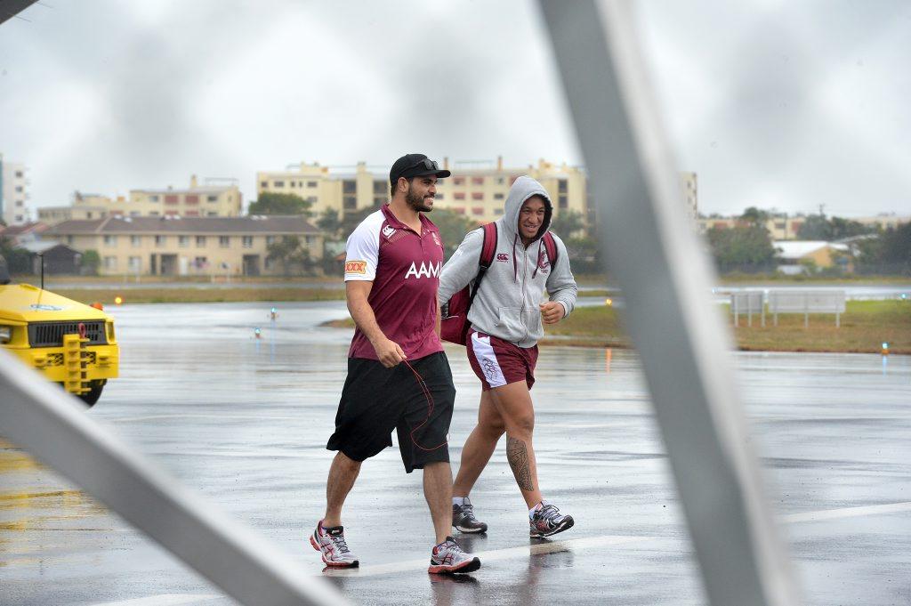 Queensland State of Origin team arrive at the Sunshine Coast Airport. Greg Inglis and Josh Papalii brave the rain. Photo: Warren Lynam / Sunshine Coast Daily