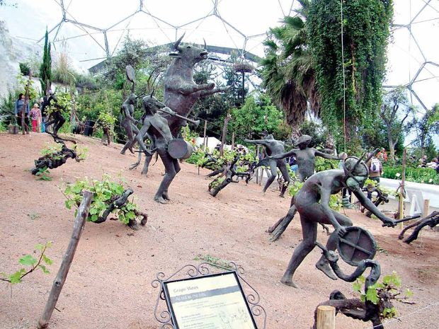 Imaginative metal sculptures of wine god Dionysus, depicted as a bull, and dancing maids are featured in a planting of grapes.