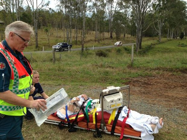 Emergency service workers with the survivor of the International Rally of Queensland crash near Imbil on Sunday. Photo: RACQ Careflight