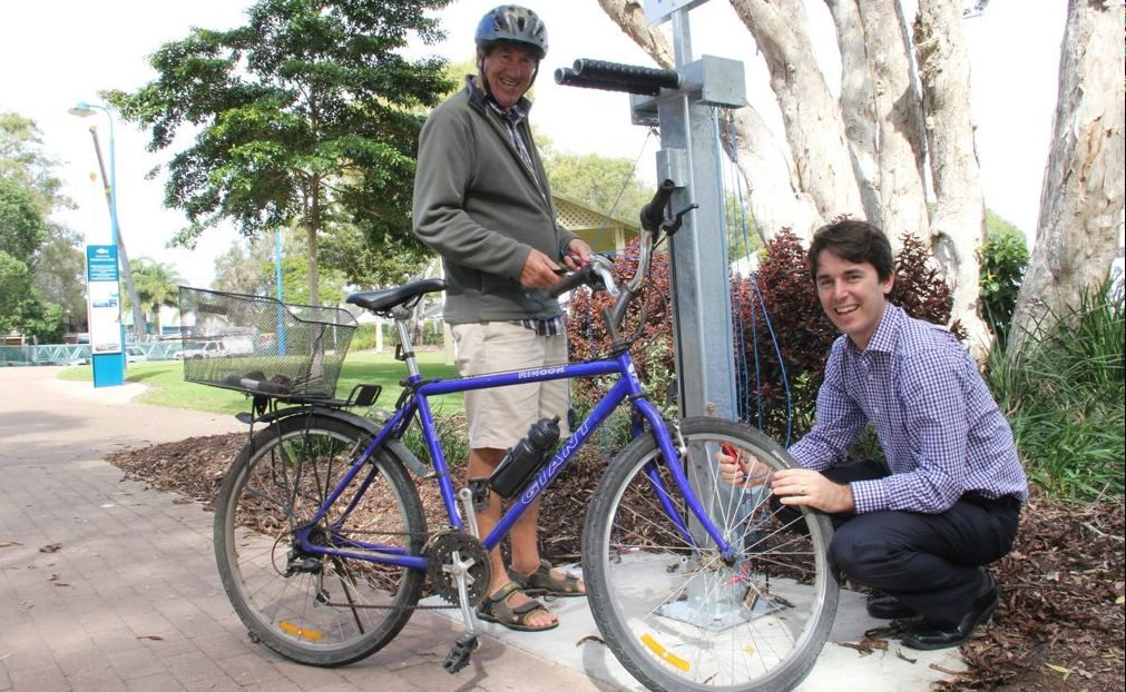 Councillor George Seymour tests out the new bike repair station in Pier Park with visiting cyclist Ian Timms from Geelong.