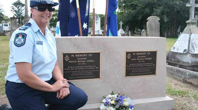 PAYING HOMAGE: Childers Senior Constable Donna Gilliland, who was stationed at Blackwater previously, kneels beside the graves of the first policers officers murdered in the Rockhampton region: Constables Patrick Cahill and John Power. Snr Const Gilliland was behind the push to have a memorial stone in place for the serving officers. Photo: Austin King / The Morning Bulletin