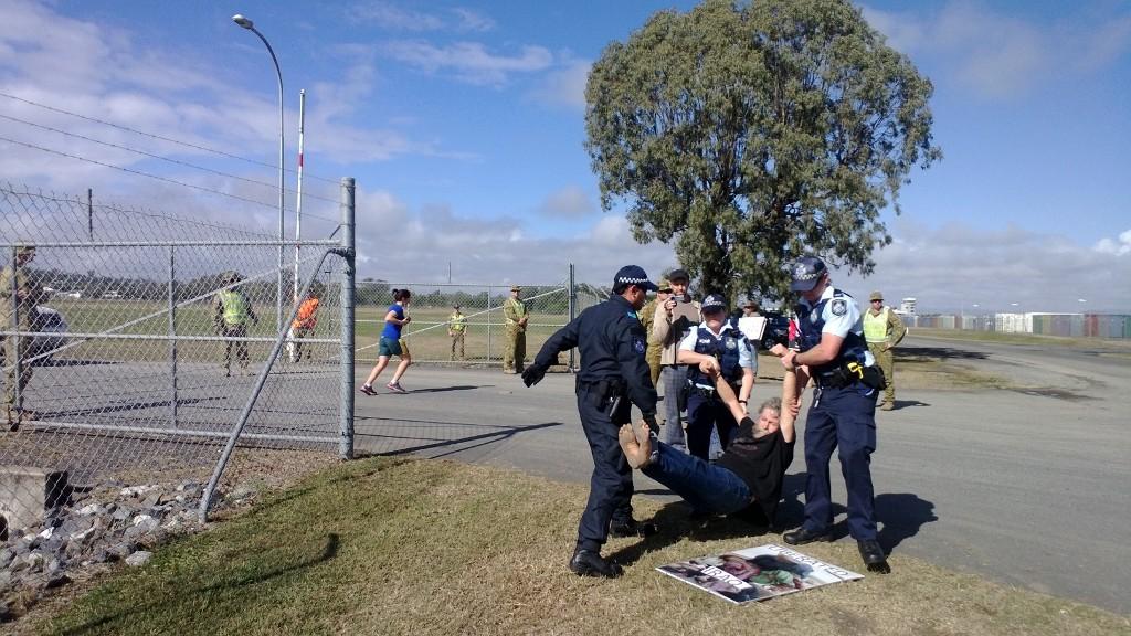 Jim Dowling being arrested outside Western Street Barracks in Rockhampton during Talisman Saber 2013.