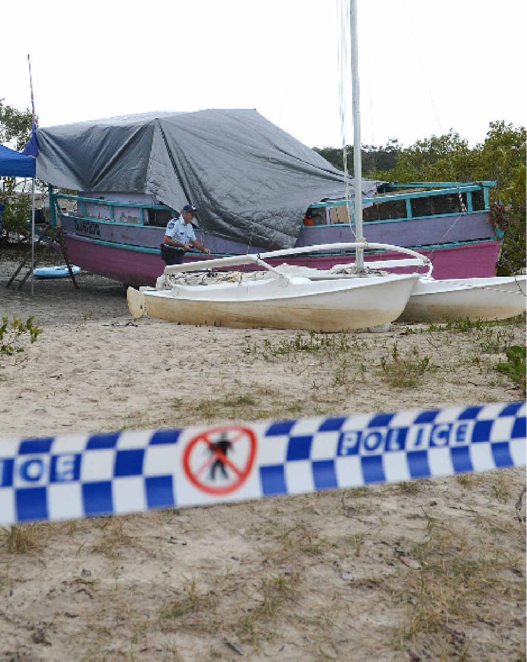 Police investigate the scene of the death of a Rainbow Beach woman at Bullock Pt yesterday.