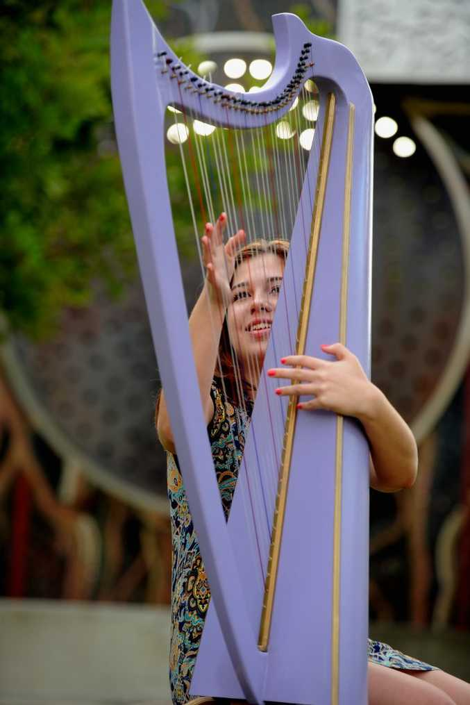John Horrex's eldest grand daughter Seinna Sunn, 14, plucks at the strings of a harp made by her grandfather.