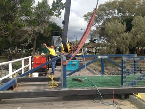 A crane is lifting a walkway into place on Urangan Pier