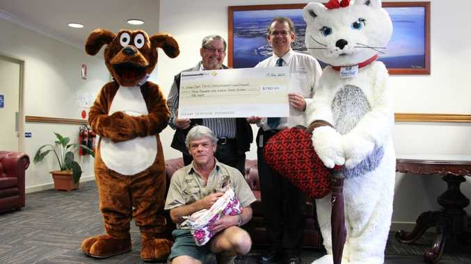 Fraser Coast Council mascots Fraser the dog and Poppins the cat help councillor Robert Garland (right) present a cheque for $3920.50 to Fraser Coast Training and Employment Support Services chief executive officer Lance Stone. They were joined by TESS wildlife ranger Ray Revill holding a two-month-old eastern grey joey orphaned after a car hit its mother.