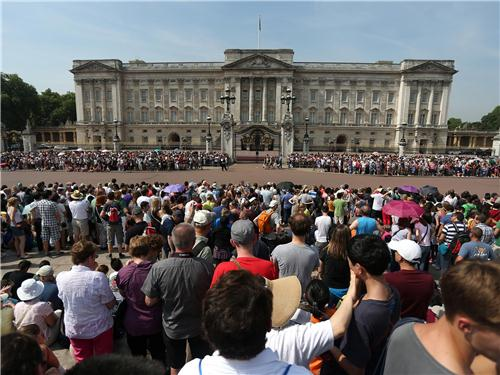 A crowd builds outside Buckingham Palace awaiting news of the royal birth.