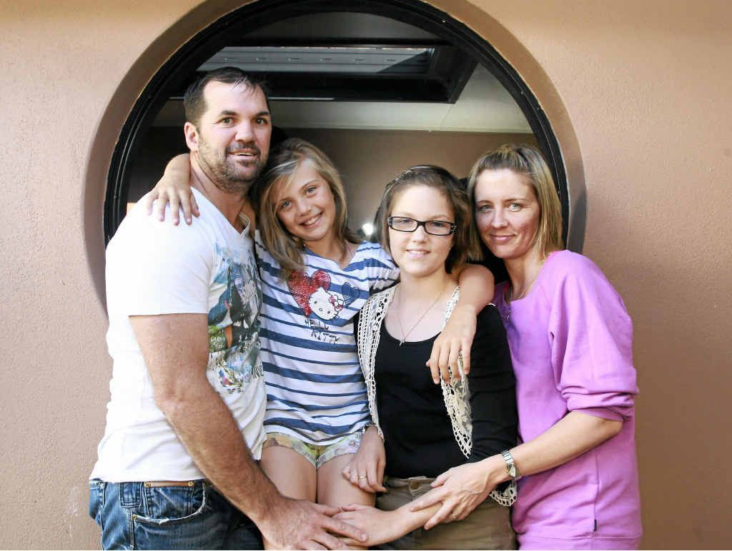HARD ROAD: Courtenay Vivian, 15, has spent the past two years in and out of hospital in Brisbane with leukemia. She is now happy to be at home with her parents Doug and Angela and her sister Bianca, 10.