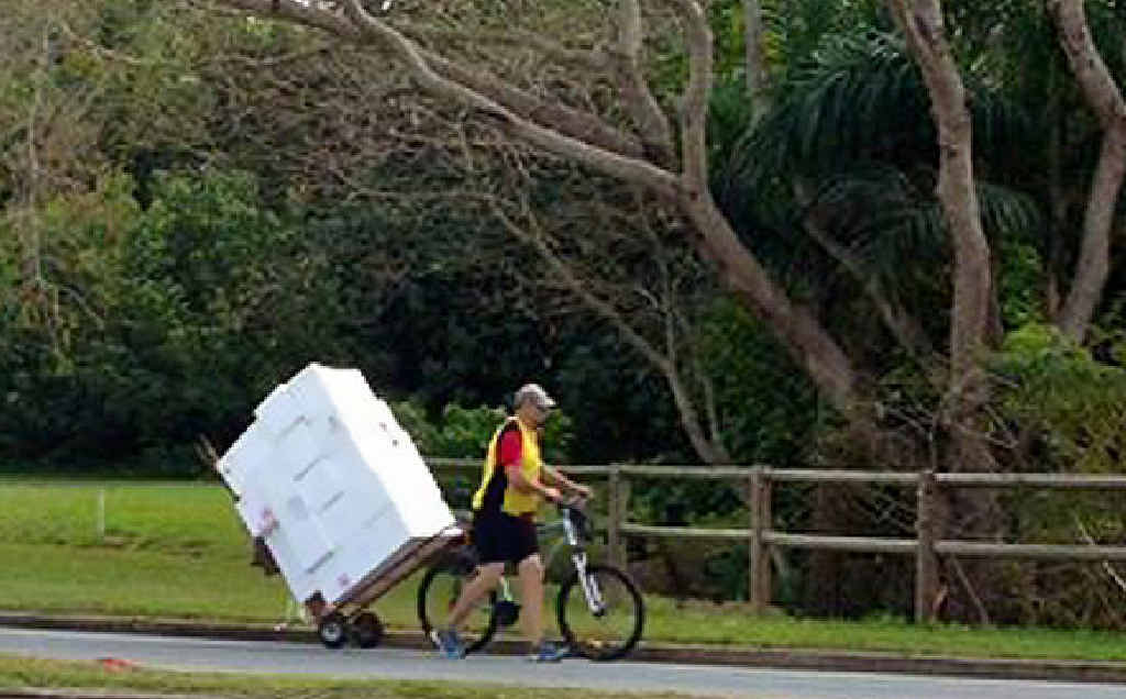 Mackay's mystery bike rider has been snapped again, this time balancing about 20 boxes on the back of his bike.