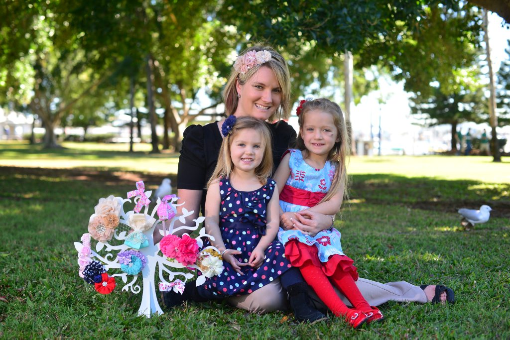 Emma Powter with children Bella, 2, Hayley, 4, has made hair pieces at home in Biloela to sell online.