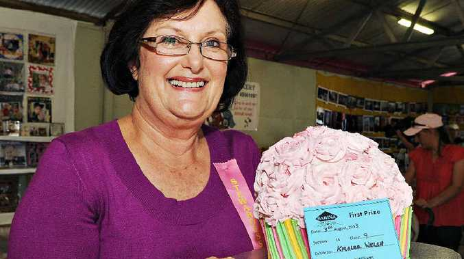 Sarina Show home economics steward Merril Williams displays a cake entered by Kiralee Welsh and judged a winner among the record number of entries.