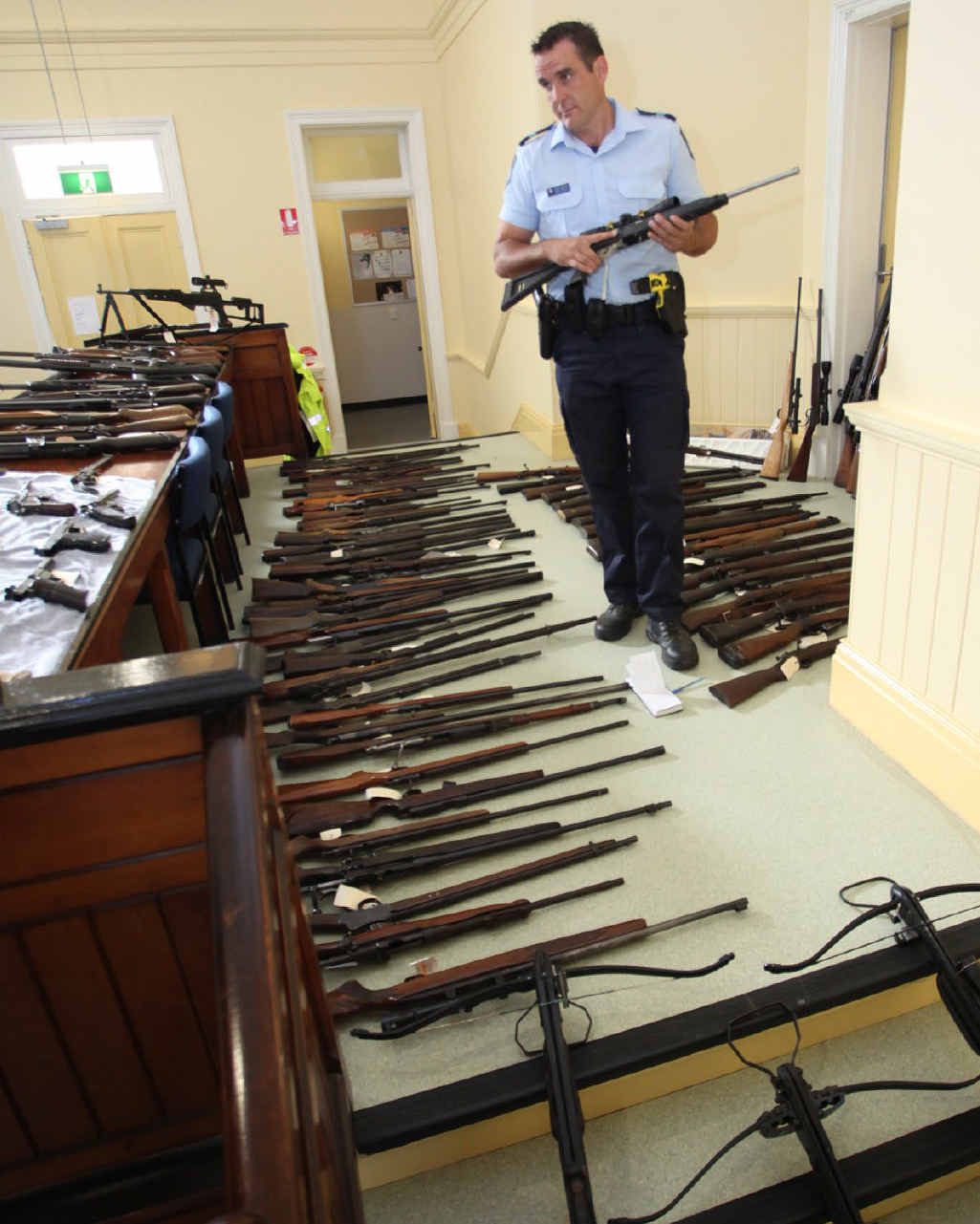 TOP COP: Senior Constable David Schultz checks some of the weapons discovered after raids on three Mt Morgan properties.