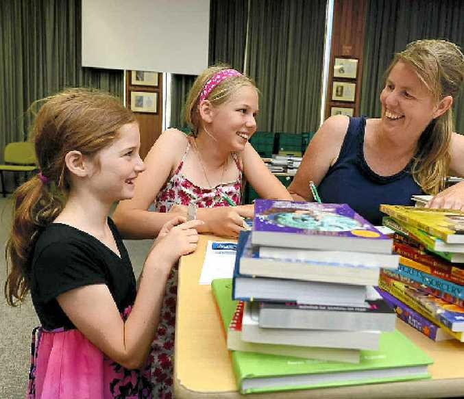 HAPPY READERS: Checking what they want to add to the library collection are Genevieve, 8, Mariah, 11 and Erin Hassett.