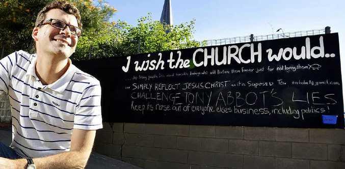 WISHFUL THINKING: Pastor Scott Muir from Central Church Ipswich next to the interactive community chalkboard on Limestone Street.