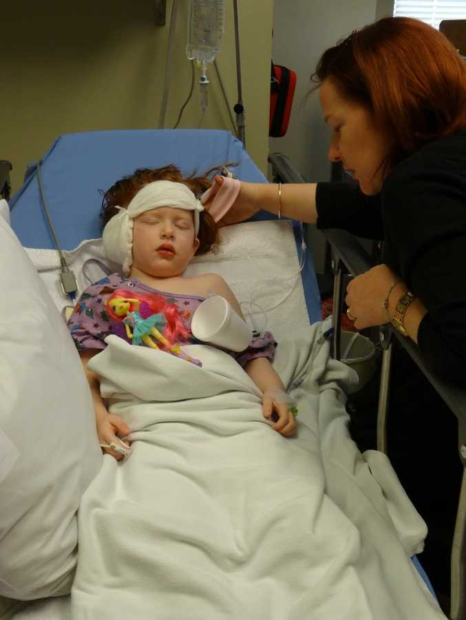 Little Alana Reid rests after the 10-hour surgery to correct her hearing.