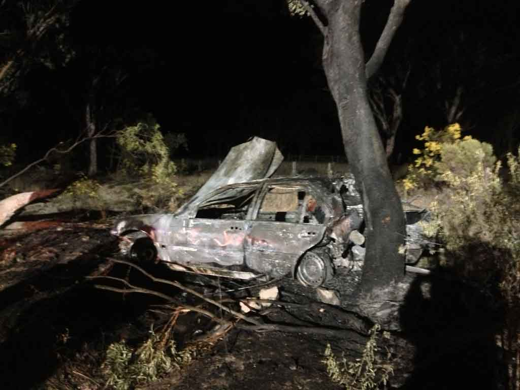The burnt out car at the crash scene.