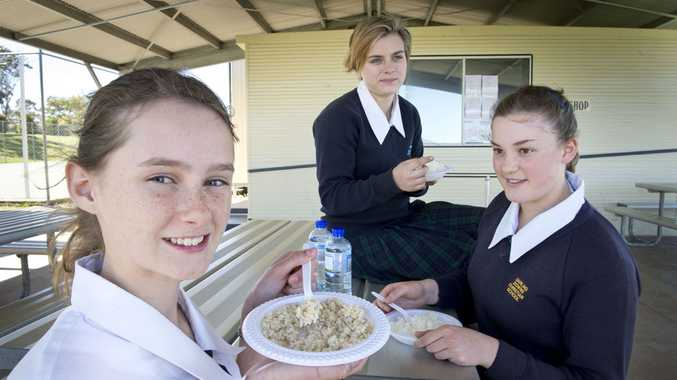 Darling Downs Christian College year nine students (from left) Hannah Wolverton, Sharna Zonter and Deanna Murphy (sitting on table) eat rice to support the Project Safe Haven charity.