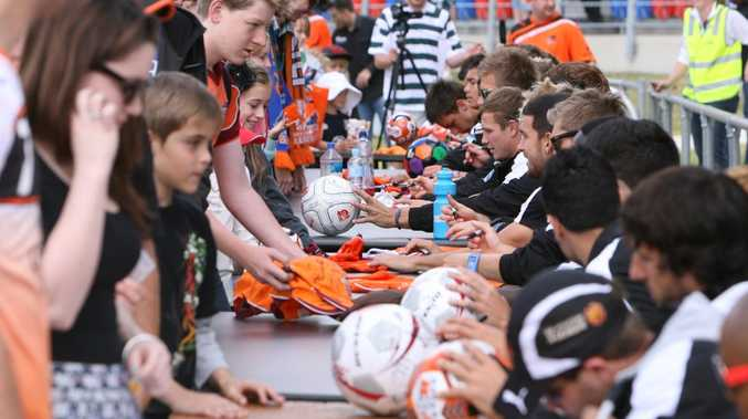 SOCCER MAGIC: Brisbane Roar players sign autographs for Ipswich fans before a match at the North Ipswich Reserve last year.