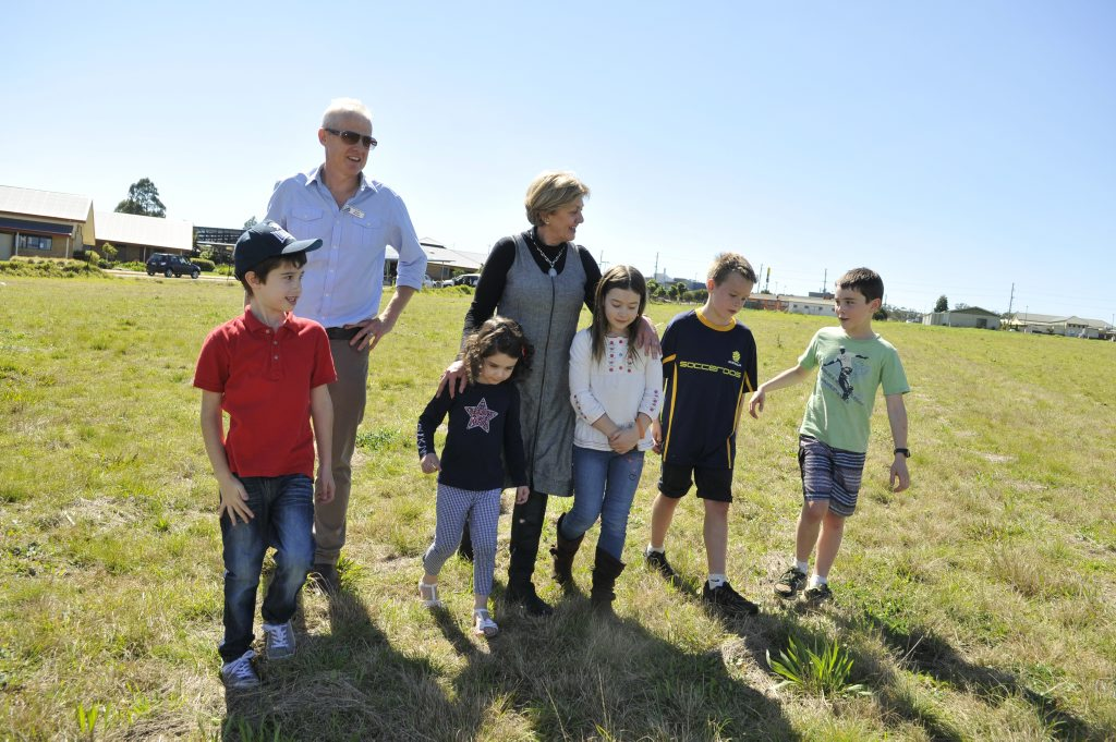 Mary MacKillop Catholic School board member Tim Ford and principal Donaugh Shirley take students (from left) Charlie Crawford, Ruby Crawford, Amelia O'Dea, Hugh Ford and Matthew O'Dea on a tour of their future high school's site.