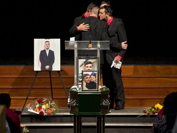 Jeremy Anderson, Mark Duggan, Alex McErlean and Zach Fitzgerald embrace at the funeral of Jaydon Adams.